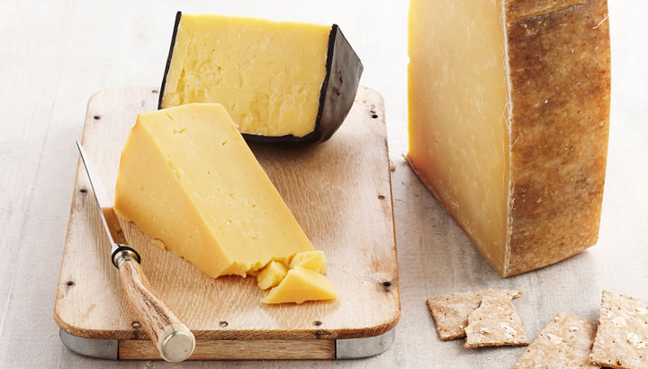 A picture of different styles of cheddar, served with crackers on a cheese platter.
